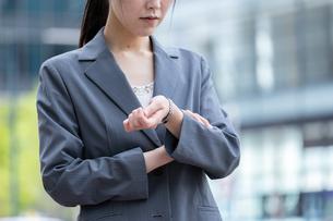 オフィス街で腕時計で時間を確認する若いビジネスウーマンの写真素材 [FYI04300804]