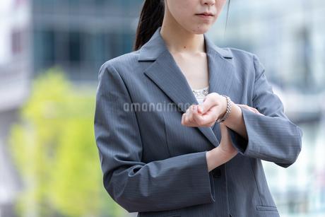 オフィス街で腕時計で時間を確認する若いビジネスウーマンの写真素材 [FYI04300805]