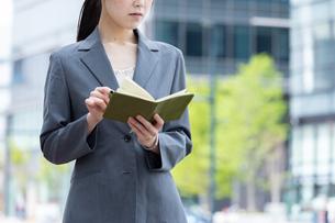 オフィス街で手帳を確認する若いビジネスウーマンの写真素材 [FYI04300806]