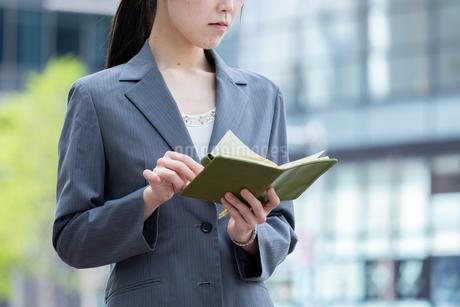 オフィス街で手帳を確認する若いビジネスウーマンの写真素材 [FYI04300807]