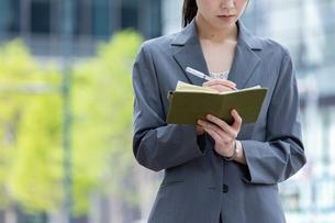 オフィス街で手帳を確認する若いビジネスウーマンの写真素材 [FYI04300808]