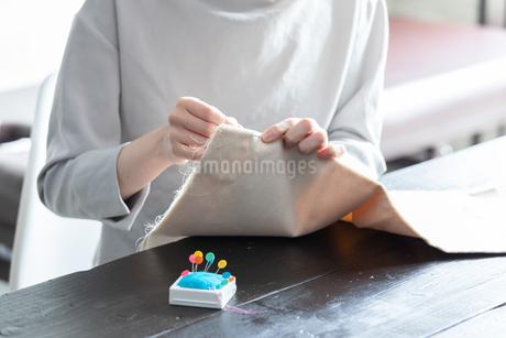 部屋の中で裁縫をする若い女性の手元の写真素材 [FYI04300815]
