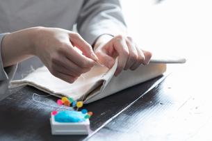 部屋の中で裁縫をする若い女性の手元の写真素材 [FYI04300817]