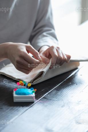 部屋の中で裁縫をする若い女性の手元の写真素材 [FYI04300818]