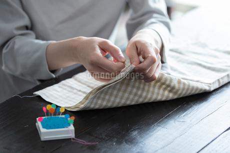 部屋の中で裁縫をする若い女性の手元の写真素材 [FYI04300819]