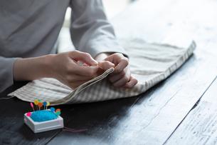部屋の中で裁縫をする若い女性の手元の写真素材 [FYI04300820]