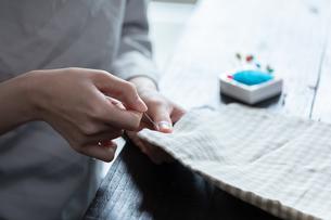 部屋の中で裁縫をする若い女性の手元の写真素材 [FYI04300821]