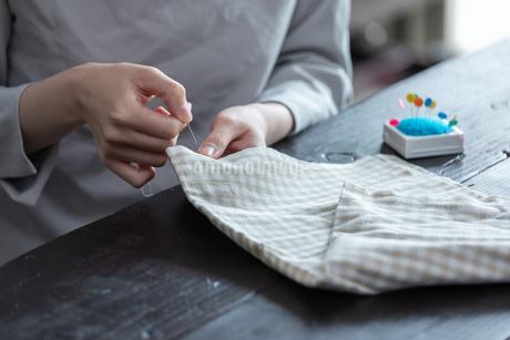 部屋の中で裁縫をする若い女性の手元の写真素材 [FYI04300822]