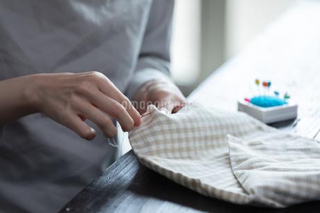 部屋の中で裁縫をする若い女性の手元の写真素材 [FYI04300823]