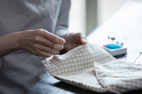 部屋の中で裁縫をする若い女性の手元の写真素材 [FYI04300824]