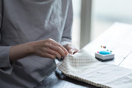 部屋の中で裁縫をする若い女性の手元の写真素材 [FYI04300825]