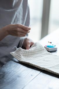部屋の中で裁縫をする若い女性の手元の写真素材 [FYI04300826]