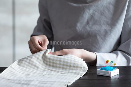 部屋の中で裁縫をする若い女性の手元の写真素材 [FYI04300827]