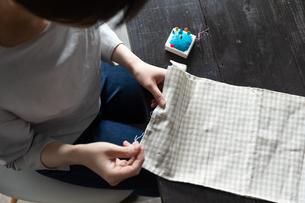 部屋の中で裁縫をする若い女性の手元の写真素材 [FYI04300828]