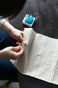 部屋の中で裁縫をする若い女性の手元の写真素材 [FYI04300829]