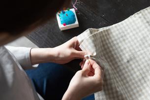 部屋の中で裁縫をする若い女性の手元の写真素材 [FYI04300830]