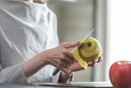 部屋の中でりんごの皮を剥く若い女性の手元の写真素材 [FYI04300831]