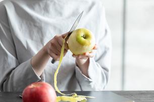 部屋の中でりんごの皮を剥く若い女性の手元の写真素材 [FYI04300833]