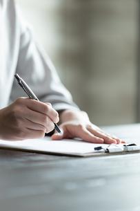 部屋で契約書にサインをする若い女性の手元の写真素材 [FYI04300839]