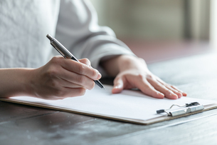 部屋で契約書にサインをする若い女性の手元の写真素材 [FYI04300840]