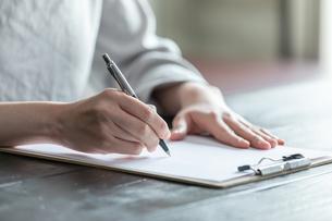 部屋で契約書にサインをする若い女性の手元の写真素材 [FYI04300841]