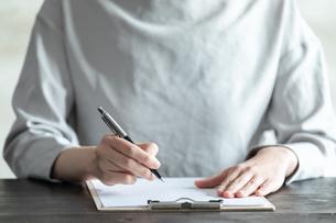 部屋で契約書にサインをする若い女性の手元の写真素材 [FYI04300842]