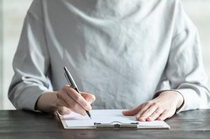 部屋で契約書にサインをする若い女性の手元の写真素材 [FYI04300843]