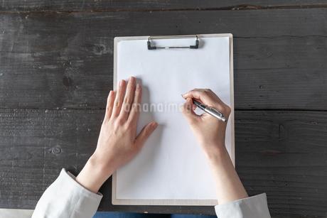 部屋で契約書にサインをする若い女性の手元の写真素材 [FYI04300845]