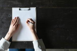 部屋で契約書にサインをする若い女性の手元の写真素材 [FYI04300846]