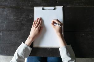 部屋で契約書にサインをする若い女性の手元の写真素材 [FYI04300847]