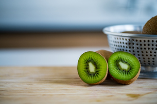 Fresh kiwifruit in the bowl on wooden cutting board.の写真素材 [FYI04300901]