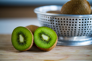 Fresh kiwifruit in the bowl on wooden cutting board.の写真素材 [FYI04300903]