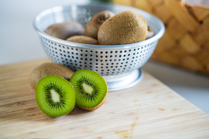 Fresh kiwifruit in the bowl on wooden cutting board.の写真素材 [FYI04300957]
