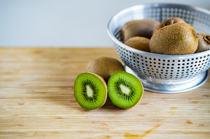 Fresh kiwifruit in the bowl on wooden cutting board.の写真素材 [FYI04300958]