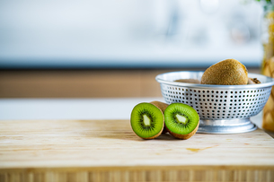 Fresh kiwifruit in the bowl on wooden cutting board.の写真素材 [FYI04300959]