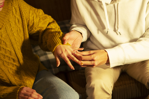 女性の薬指に指輪をはめる男性の手元の写真素材 [FYI04301176]