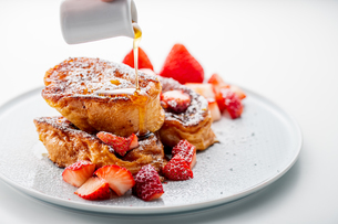 French toast with fresh strawberries and honey syrup on white plate. Delicious dessert image.の写真素材 [FYI04301263]