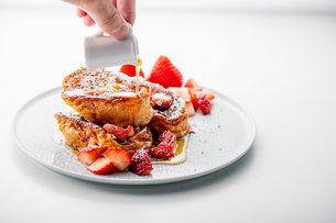 French toast with fresh strawberries and honey syrup on white plate. Delicious dessert image.の写真素材 [FYI04301264]