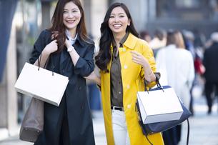 街中で微笑む2人の女性の写真素材 [FYI04301923]