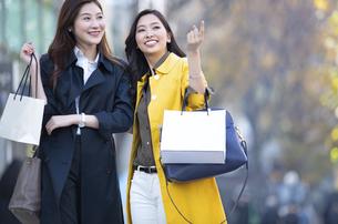 街中で指を差した方向を見る2人の女性の写真素材 [FYI04301924]