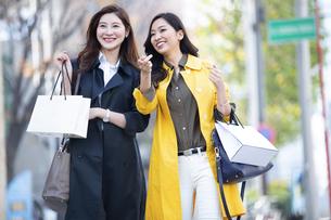 街中で指を差した方向を見る2人の女性の写真素材 [FYI04301925]