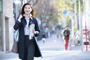 微笑みながら街中を歩く女性の写真素材 [FYI04301929]