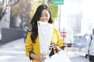 街中で花束を見る女性の写真素材 [FYI04301930]