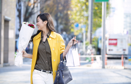 街中で花束の香りをかぐ女性の写真素材 [FYI04301931]