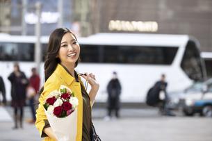街中で花束を持って微笑む女性の写真素材 [FYI04301932]