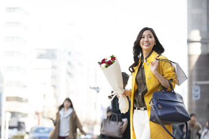 街中で花束を持って立つ女性の写真素材 [FYI04301934]