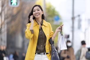 街中で電話で話す女性の写真素材 [FYI04301935]