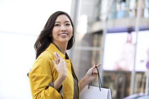 街中でショッピングバッグを持って振り返る女性の写真素材 [FYI04301936]