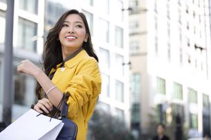 街中でショッピングバッグを持って振り返る女性の写真素材 [FYI04301937]