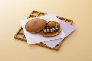 オレンジのテーブルで木のお皿に乗った栗入りのどら焼きの写真素材 [FYI04302081]